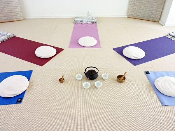 Farbige Yogamatten, Klangschalen und Tee angerichtet auf dem Boden